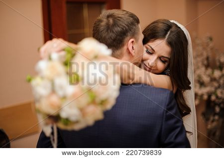 elegant brunette bride with a bouquet of roses hugs a stylish bridegroom, while he kisses her