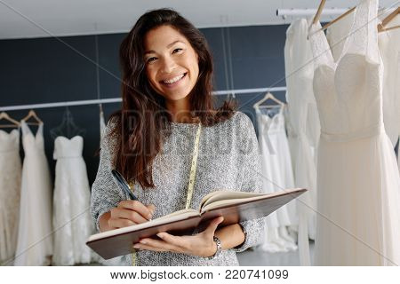 Female bridal store owner with a diary. Female tailor working in bridalwear store.
