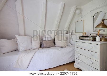 Small cottage bedroom beutifully decorated in shades of white with quilt covered daybed, matching pillows, chest of drawers, mirror, perfume botttle and contrasting jewelry box