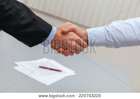 Business handshake after signing the contract. Two businessman shaking hands. stock photo