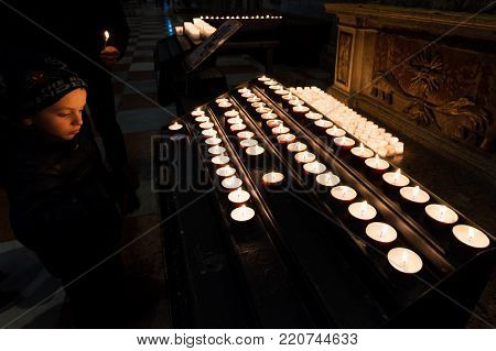TRENTO, ITALY - DECEMBER 29, 2016: A boy looks at the tea light candles in a church of Trento, Italy on December 29, 2016