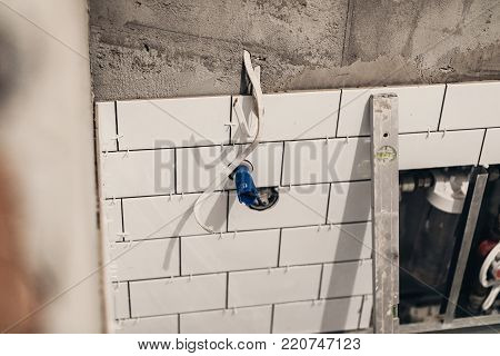 bathroom renovation concept. pipes drainage and white stylish tiles on wall in bathroom, renovating and working in toilet, space for text