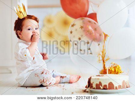 funny infant baby boy tasting his 1st birthday cake