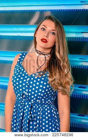 portrait of beautiful attractive pretty long haired young woman in polka-dot blue dress with stylish make up in pin up style on the blue background