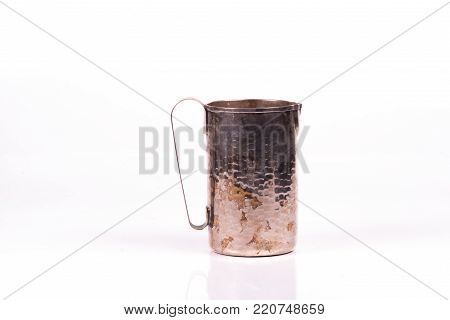 handcrafted antique silver cup water over a white background