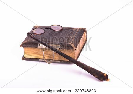 antique eye glasses and book ove a white background