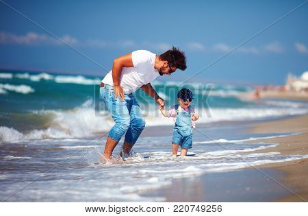 playful father and toddler son having fun jumping in sea waves during summer vacation, family leisure activity games