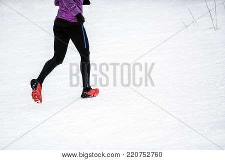 Trail running woman in winter mountains. Sport, fitness inspiration and motivation. Young happy woman cross country running in mountains on snow, winter day. Female trail runner jogging outdoors.