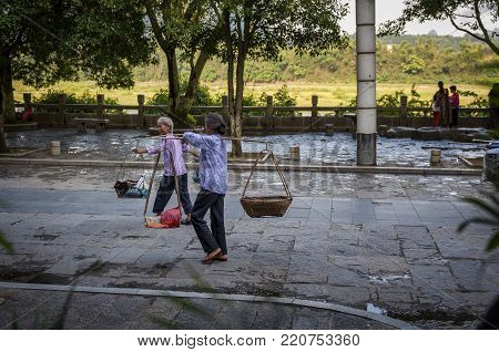 Yangshuo, China - August 1, 2012: Two chinese woman carrying agricultural products on shoulder poles in a street of the town of Yangshuo in China, Asia.