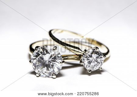 Two diamond engagement rings with gold bands on a white background