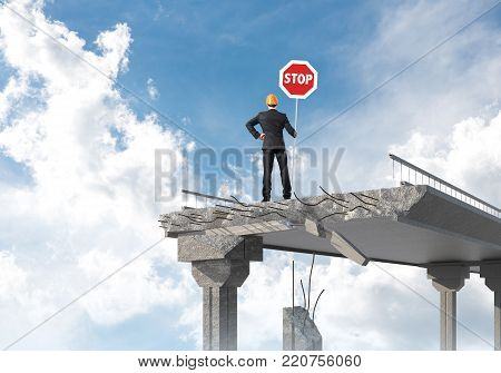 Rear view of engineer in helmet holding stop sign while standing on broken bridge with skyscape on background. 3D rendering. poster