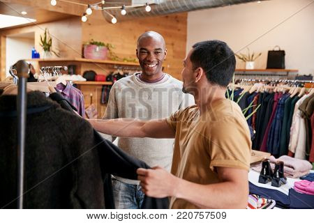 Two young men shopping for clothes in a clothes shop