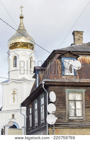 Russian orthodox church near the old wooden house with satellite dishes