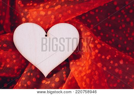 Plywood heart on the red tulle textile
