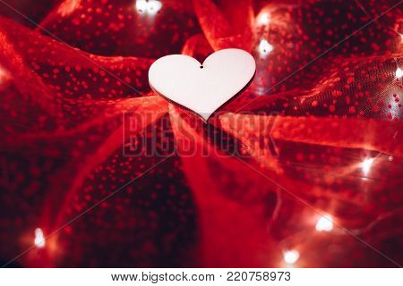 Plywood heart on red tulle textile with lights garland