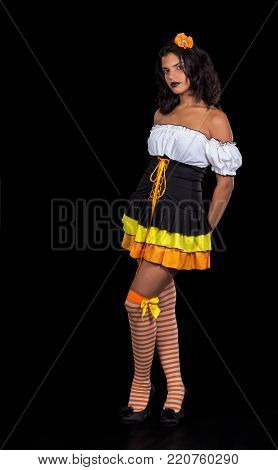girl dressed as doll portrayed on black background