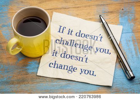 If it doesn't challenge you, it doesn't change you - handwriting on a napkin with a cup of coffee