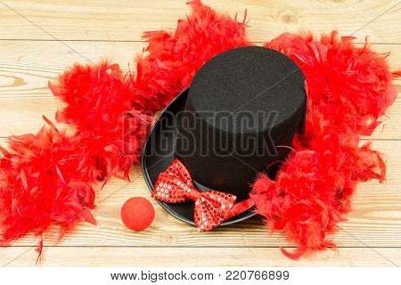 black tall hat, red fluffy feather boa, red bow tie and red clown nose on wood background. Carnival accessory.