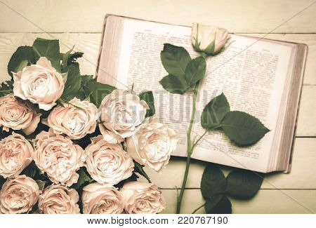 Roses bouquet and an open book in retro style - Vintage image with a bouquet of roses in the foreground and an old open book with a single rose on it in the background, placed on a wooden table.