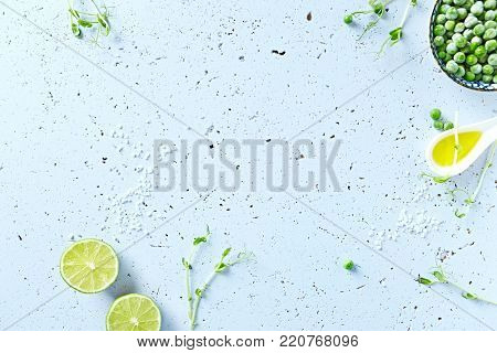 Symbolic food background with lime, pea sprouts, sea salt and frozen peas