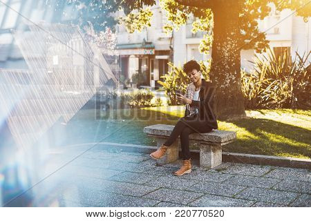 Happy sweet Brazilian girl is sitting in park on concrete bench and taking selfie or photo shooting via her mobile cell phone on a sunny day, copy space area with chromatic aberrations for your advert
