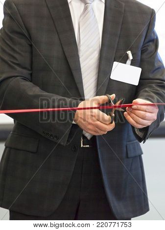 The image of scissors in the hand cuts the red tape.