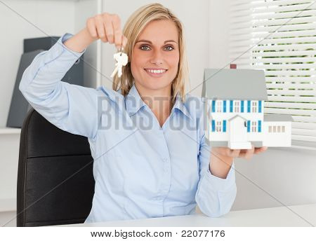 Gorgeous Businesswoman Presenting Model House And Keys Looks Into Camera