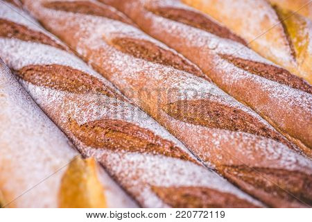 Rye baguettes lie next to each other in flour. White flour lies on light and rye baguettes. Fresh baguettes lie on a wooden table. Baguettes of different flour lie close to each other closely. Close-up.