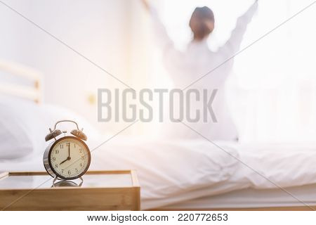 Close Up Alarm Clock. Happy Woman Stretching On Bed After Waking Up In The Early Morning At Window S