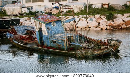 Wooden sinking dilapidated fishing boat in Lagos Portugal