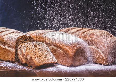 White flour is poured onto a loaf of rye bread. Loaves of rye bread lie next to each other. Sliced pieces of bread lie near the loaf. Bread is strewn with white flour.