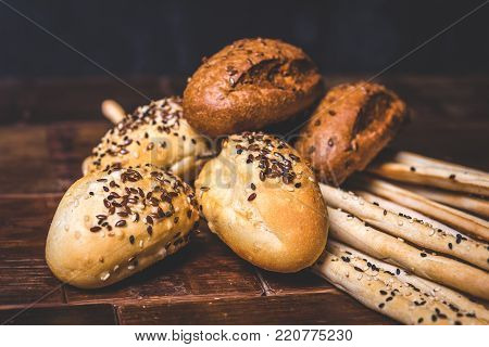 Buns and bread sticks lie on a wooden table. Buns of wheat and rye flour lie on bread sticks. Baking is strewn with seeds.