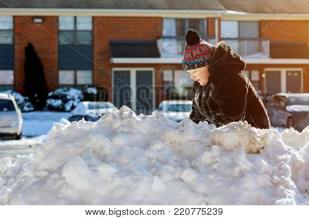 Little girl shoveling snow on home drive way. Beautiful snowy garden or front yard. Child with shovel playing outdoors in winter season. Kids play outside.