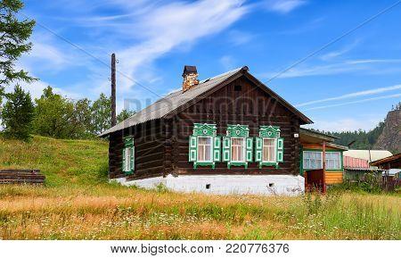 BOLSHIYE KOTY, IRKUTSK REGION, RUSSIA - July 24, 2017: Wooden Russian hut with green shutters on windows. Traditional dwelling in Siberian villages with autonomous heating by firewood