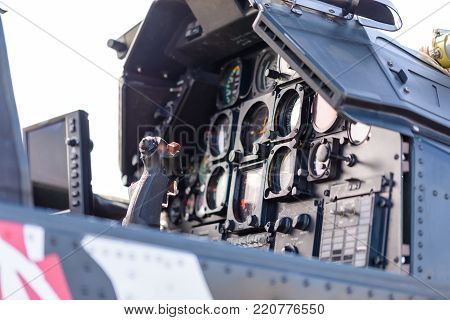 Detailed, close up view of military attack helicopter cockpit with control stick and dashboard with instruments and displays