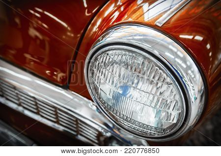 Color detail on the headlight of a vintage car. Horizontal