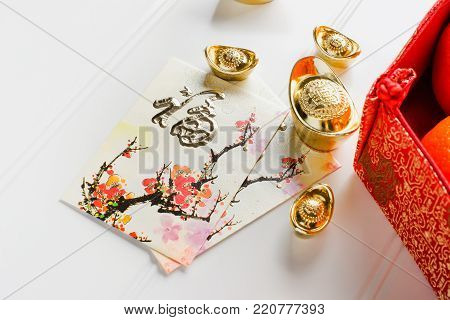 Chinese New year,red envelope packet (ang pow) and red felt fabric bag with gold ingots and oranges and flower on white wood table top,Chinese Language mean Happiness and on ingot mean wealthy.