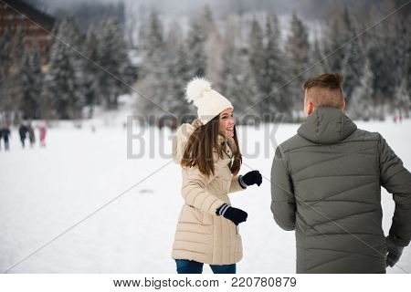 Man chasing his partner outdoors on snow