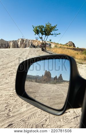 Reflection of the mountain with an ancient dwelling in the car mirror. Cappadocia.