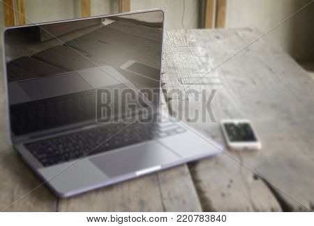 Modern grey metal laptop and smart phone on wooden table, stock photo