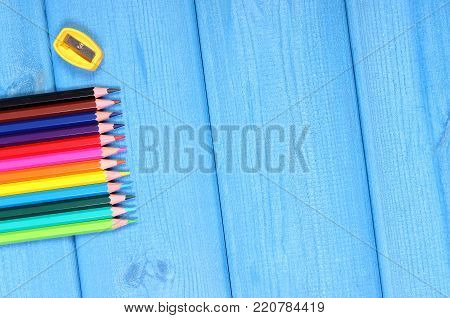 Colorful crayons and sharpener, school supplies and accessories, copy space for text on blue boards