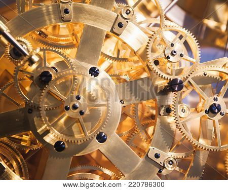 Vintage clock mechanism, fragment with many shiny gears