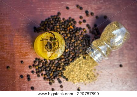 Close Up Of Oil Of Black Pepper,piper Nigrum With Raw Black Pepper And Powder On A Wooden Surface.