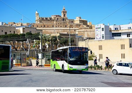 VICTORIA, GOZO, MALTA - APRIL 3, 2017 - Green and white Malta public transport bus in the port area with views towards the citadel, Victoria (Rabat), Gozo, Malta, Europe, April 3, 2017.