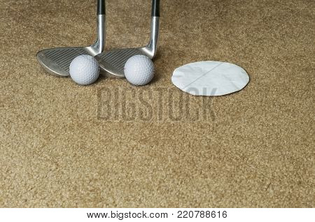 Two golf club wedges, two golf balls, and paper cut-out representing putting cup on an indoor carpet.
