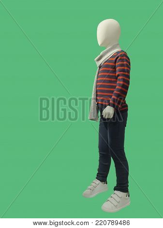 Child mannequin dressed in casual clothes, isolated on green background. No brand names or copyright objects.