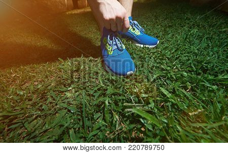 Tying blue running shoes closeup on green grass background. Tie laces on sport shoes outdoor