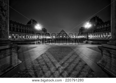 PARIS, FRANCE - DECEMBER 02, 2017: Black and white view of famous Louvre Museum with Louvre Pyramid at night. Louvre Museum is one of the largest and most visited museums worldwide