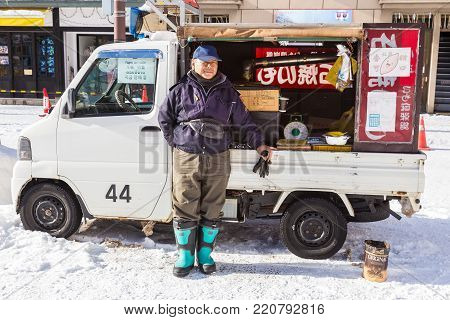 Otaru, Hokkaido, Japan - 30 December 2017, Baked sweet potato food vendor man waits patiently by his converted grilled mini truck for customers to buy his baked sweet potatos in Otaru, Hokkaido, Japan on a cold winter day of December 30, 2017
