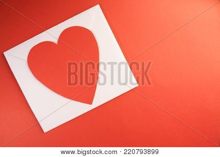 a white envelope with a bright red paper heart ontop of it against a white background template